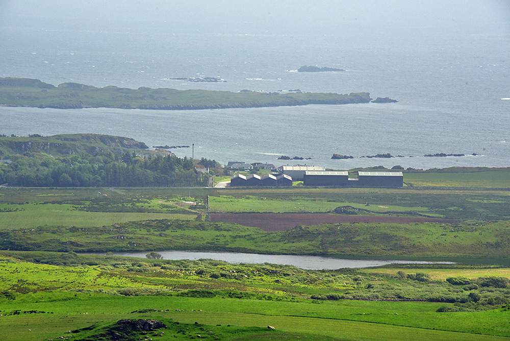 Picture of a coastal distillery and a reservoir seen from hills