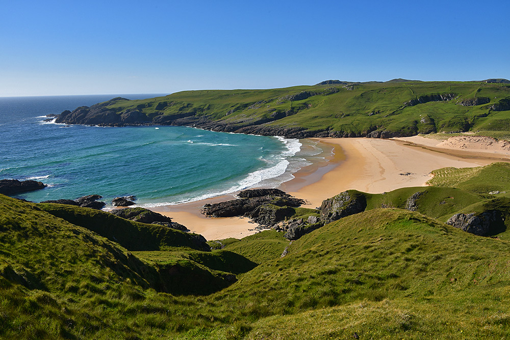 Picture of a bay with a sandy beach in bright sunshine under a blue sky