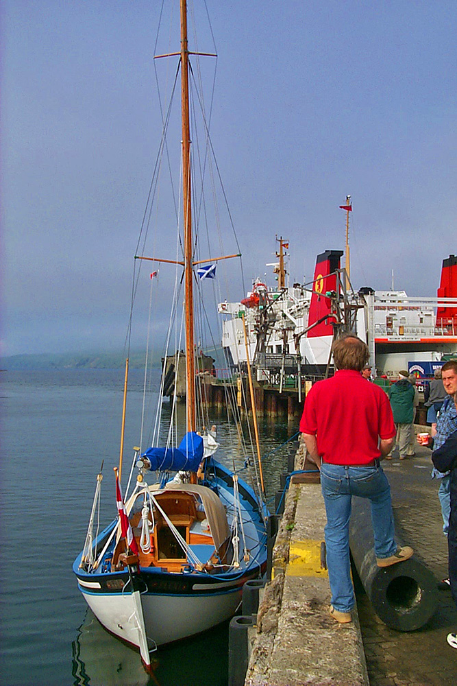 Picture of a sailing boat at a pier, a ferry in the background