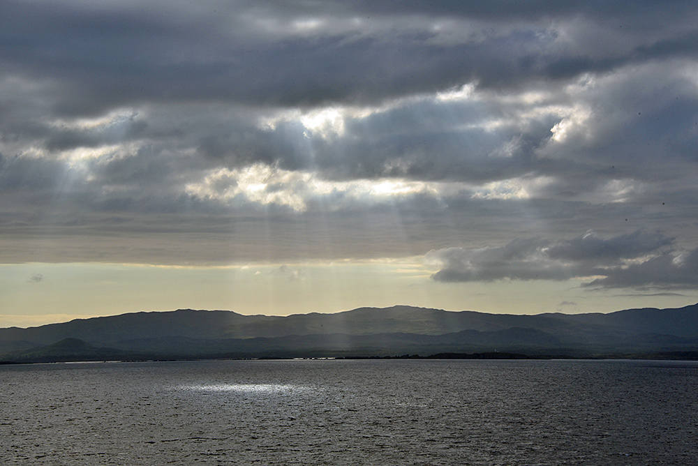 Picture of the sun breaking through clouds sending sunrays down over a coast