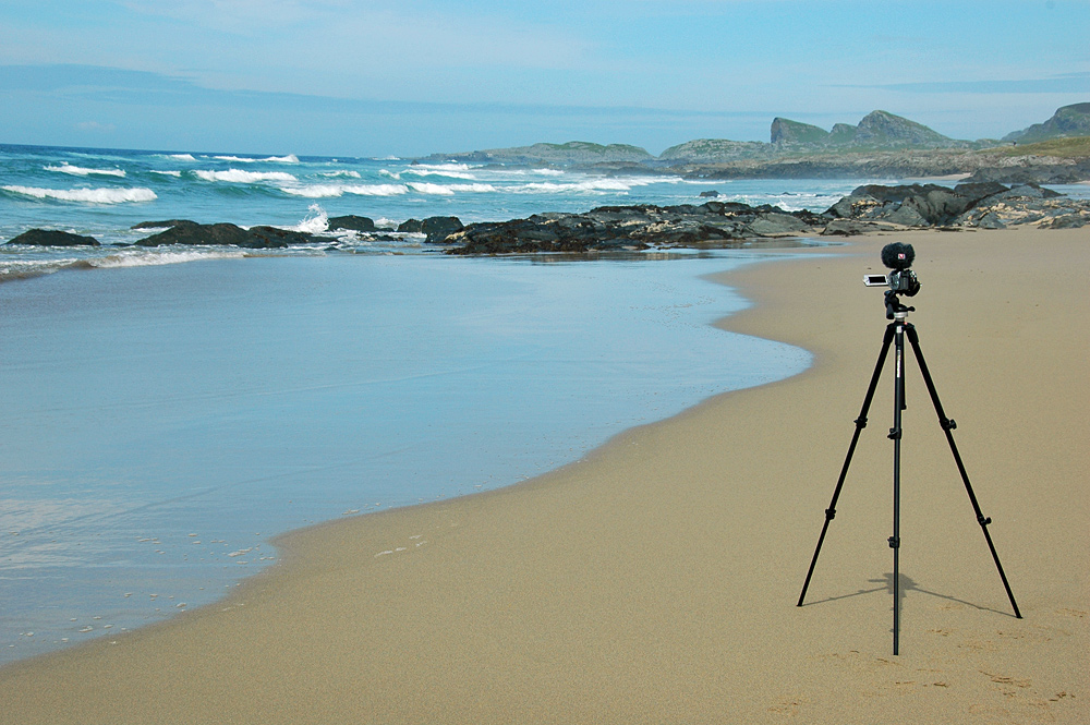 Picture of a video camera on a tripod on a beach
