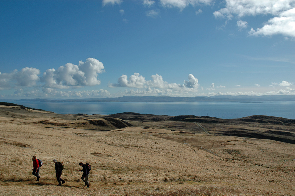 Picture of some walkers ascending a low hill near a coast