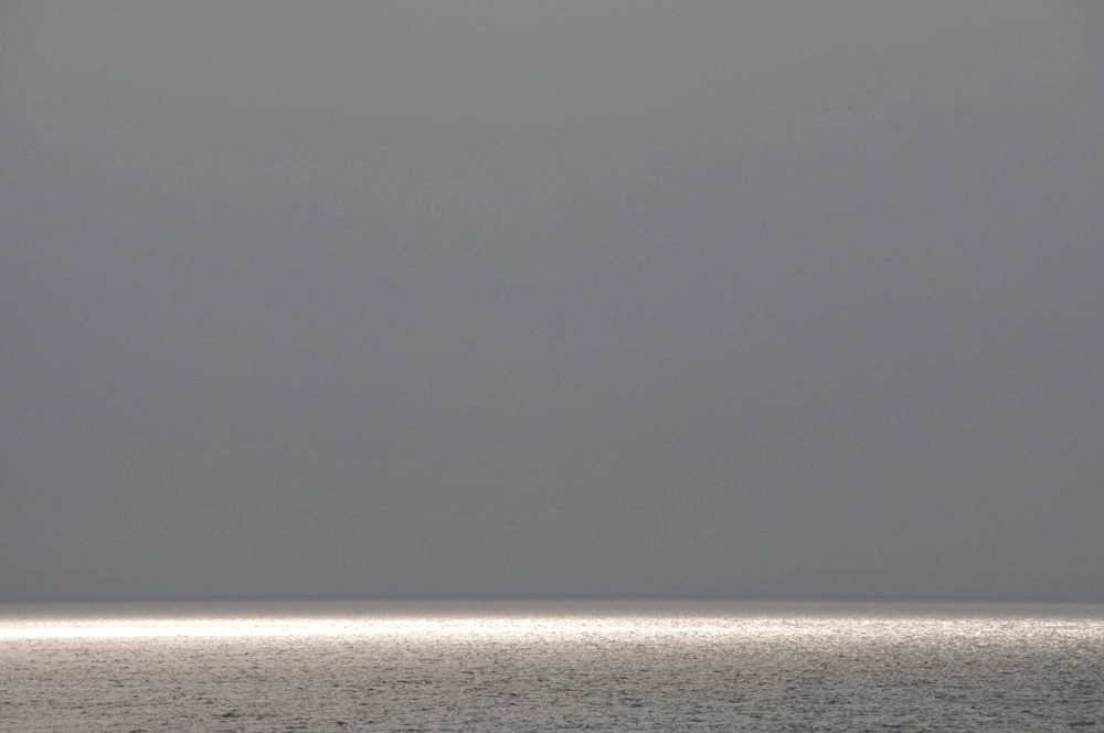 Picture of bright sun reflecting off the sea under a dark grey sky