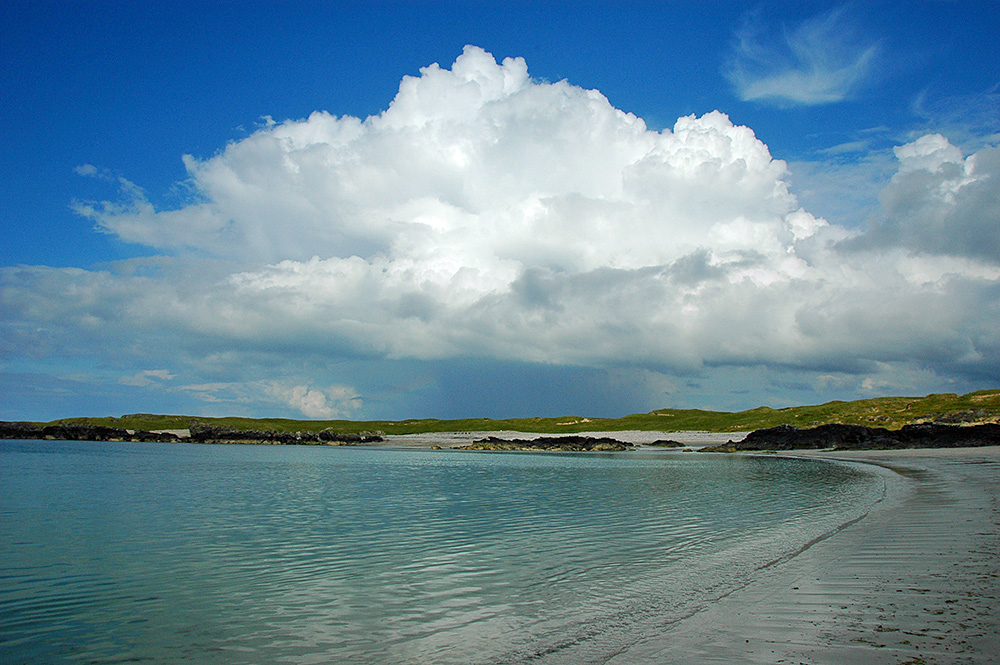 Picture of a dramatic big cloud over a small bay with a beach