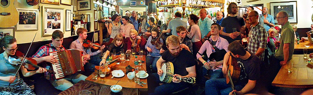 Panoramic picture of musicians and visitors in a hotel pub