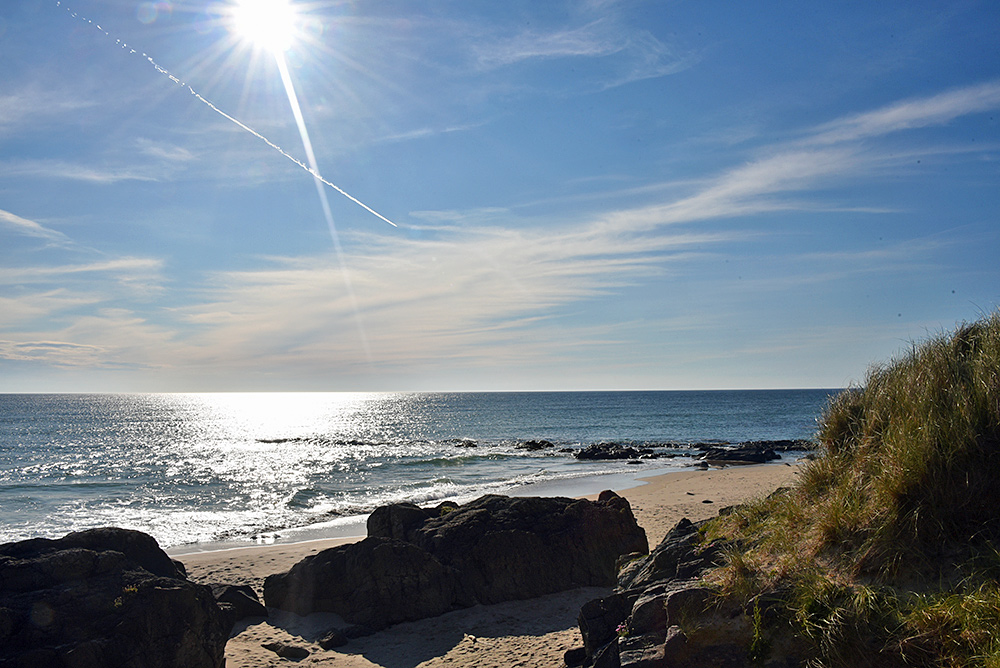 Picture of a view over a beach in the sun with the contrail from a plane visible in the sky