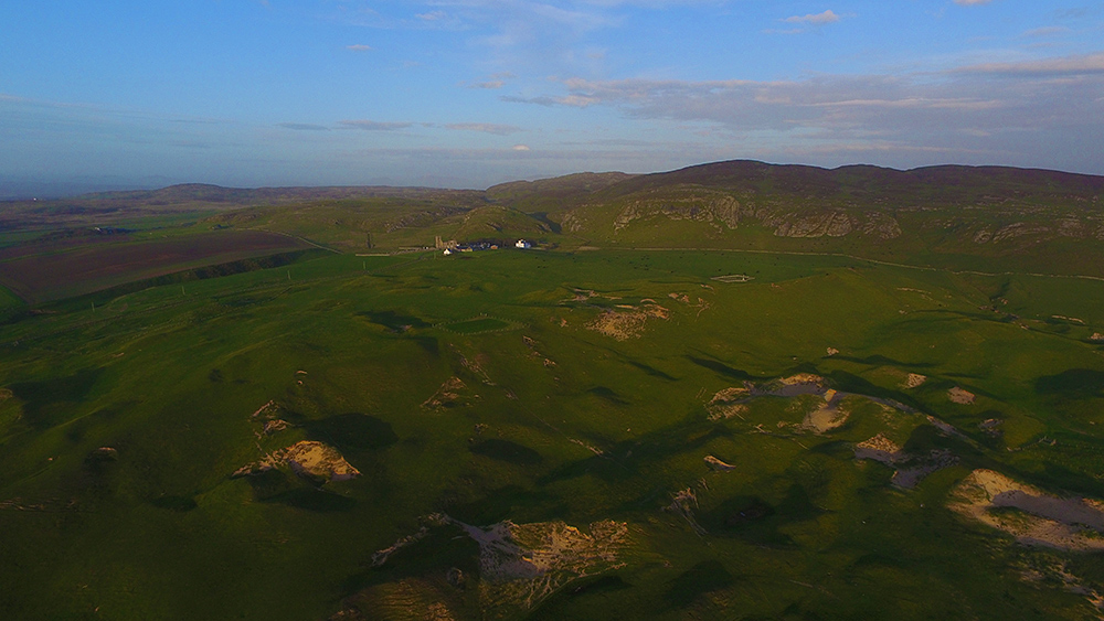 Picture of a small settlement with a church, manse and houses below crags and behind dunes, seen from the air