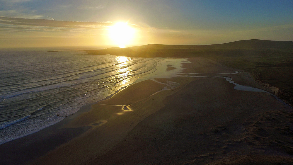 Picture of a sunset over a bay with a wide sandy beach seen from the air