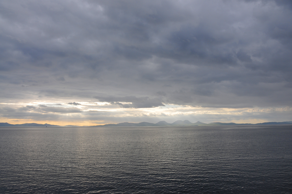 Picture of a mostly cloudy view from a ferry, two islands in the distance
