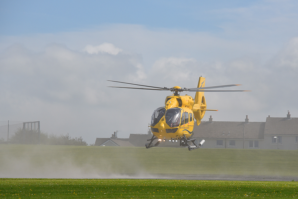 Picture of a yellow helicopter blowing up dust as it lifts off
