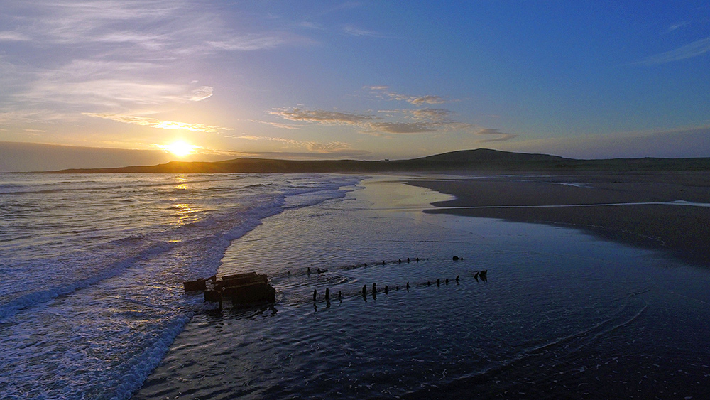 Picture of a sunset over a wreck on a beach, seen from the air with a drone