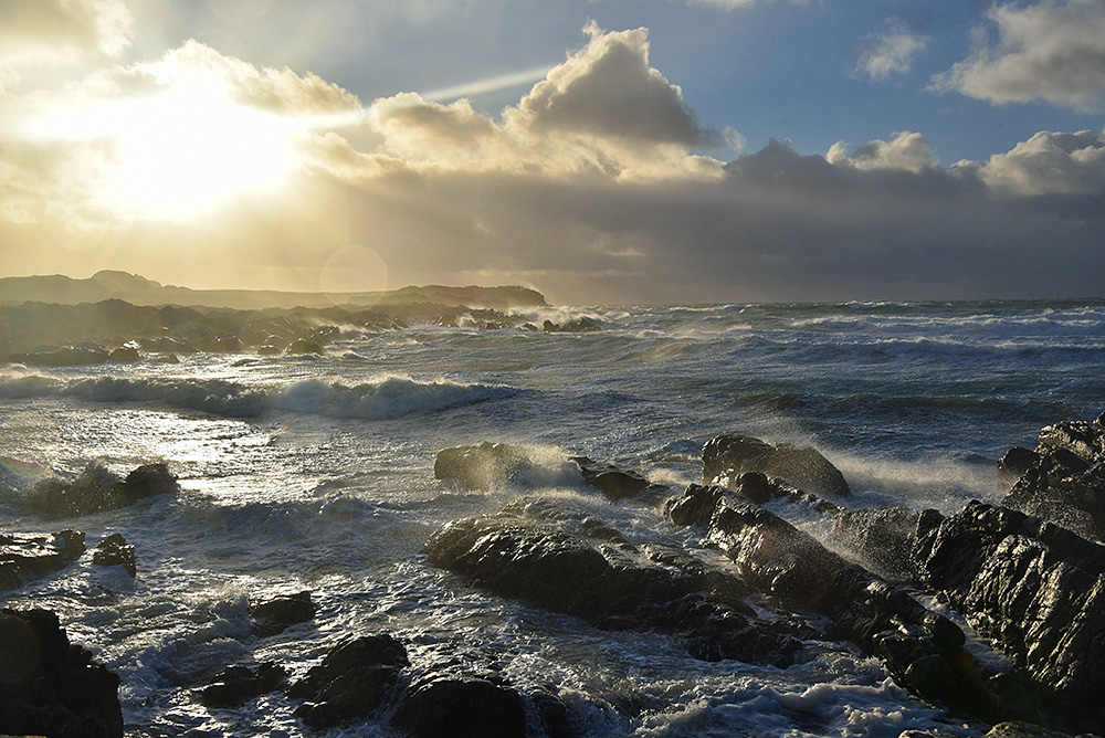 Picture of waves breaking over rocks in a bay, sun breaking through clouds