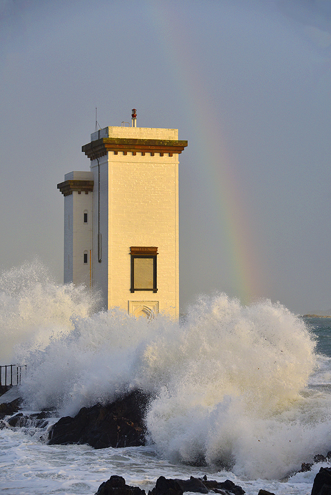 Picture of a square lighthouse with waves breaking around it, a rainbow in the background