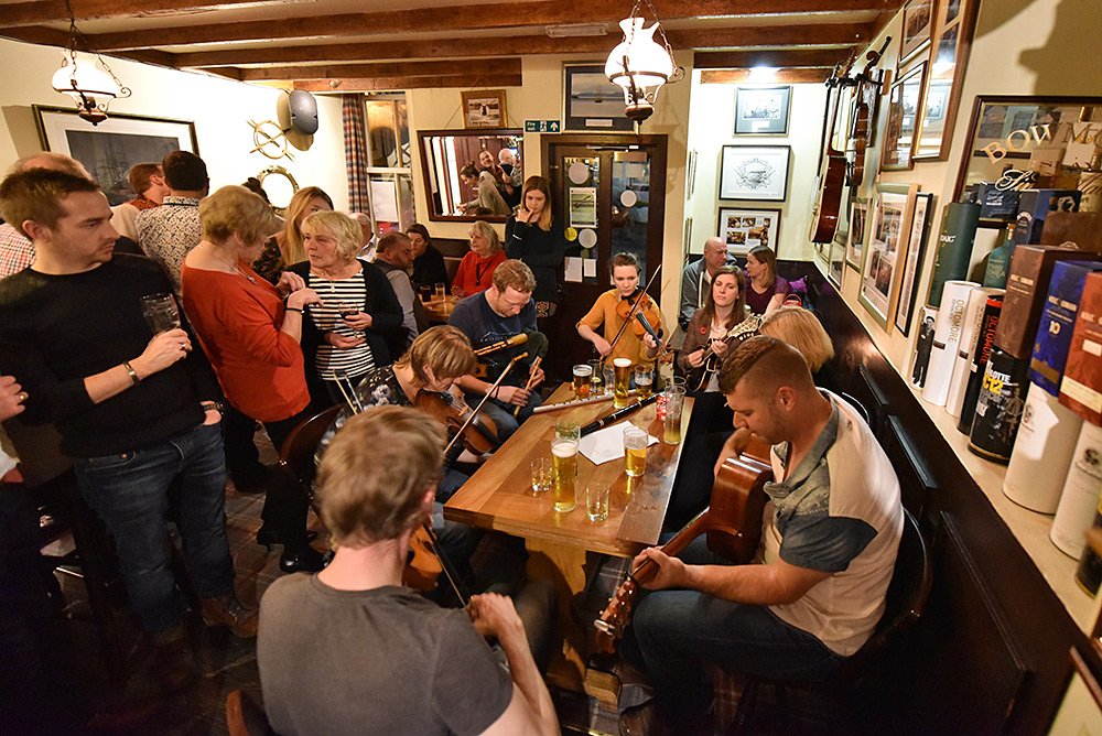 Picture of a group of musicians playing in a busy pub
