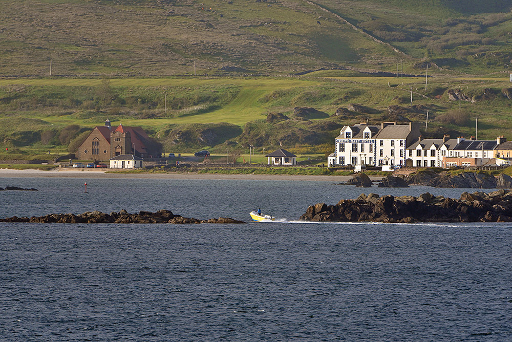 Picture of a small yellow motorboat passing between rocks as it approaches a coastal village