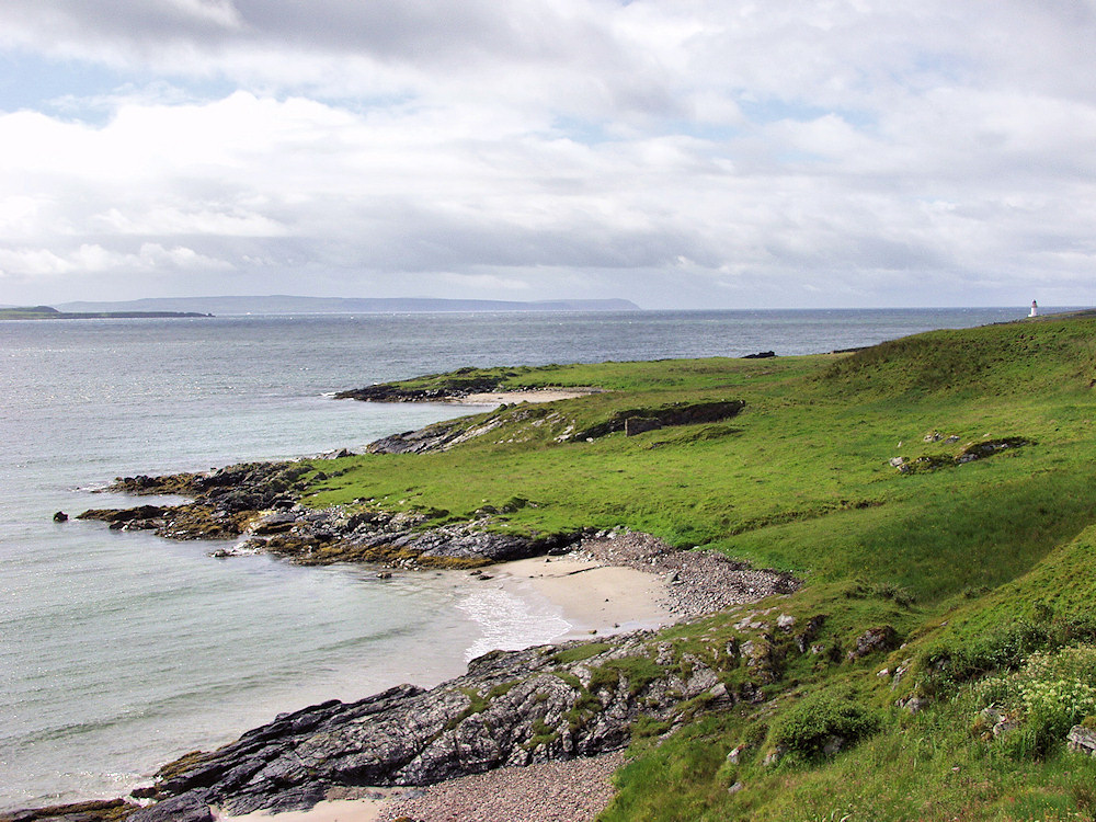 Picture of two small beaches along a coast, a lighthouse in the distance
