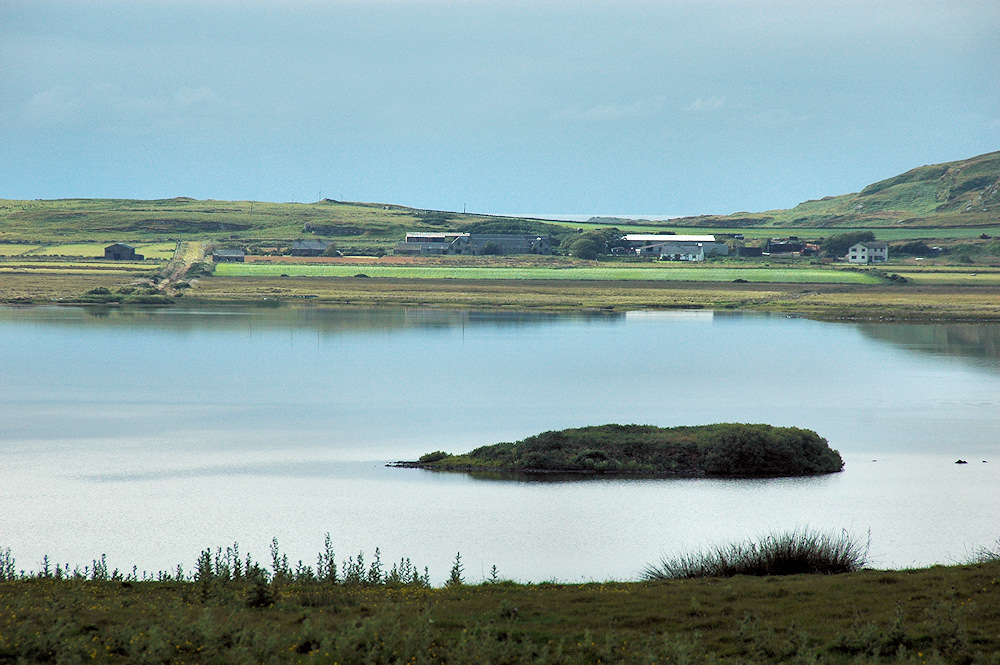 Picture of a loch (lake) with a small crannog island, a farm settlement on the other side