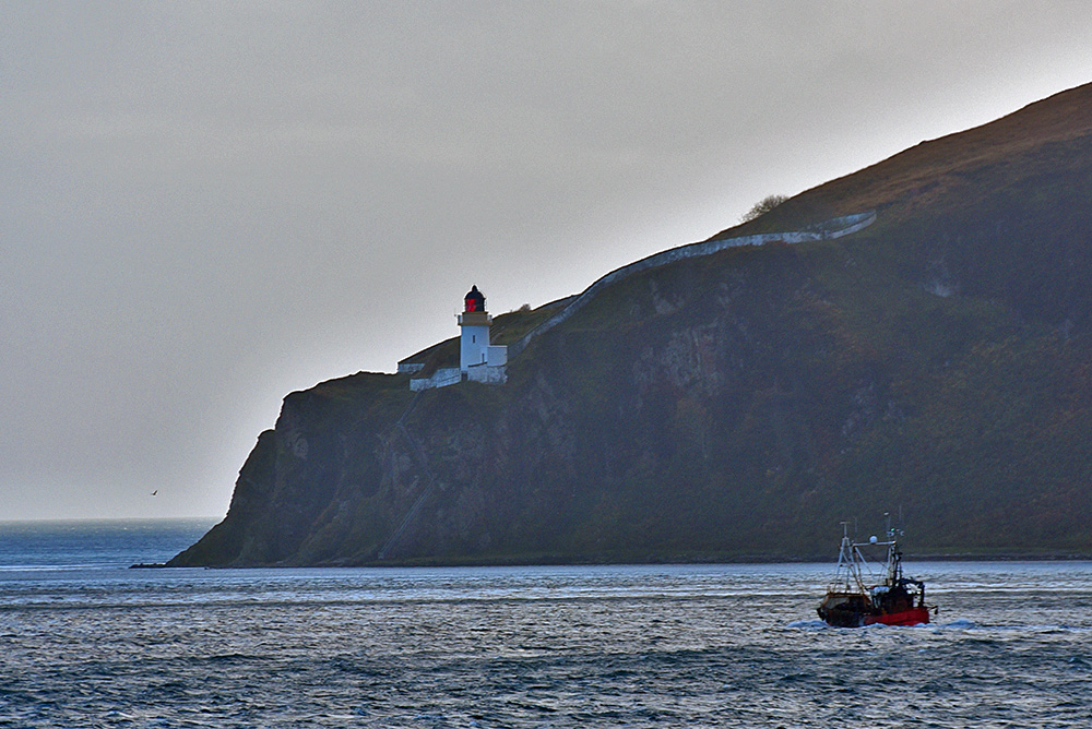 Picture of a fishing boat passing a lighthouse high on steep cliffs