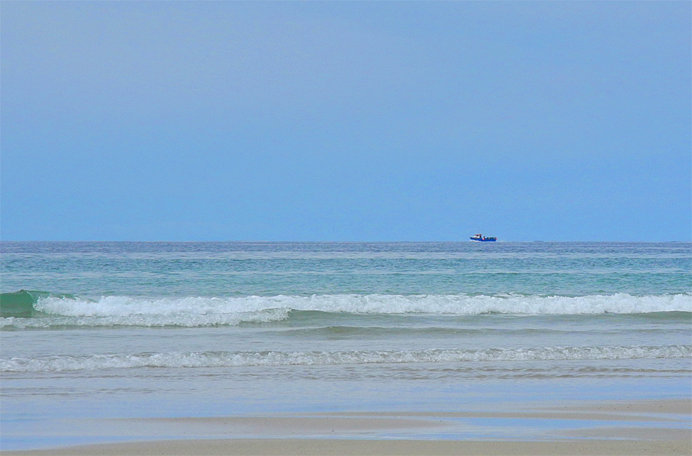 Picture of a view out to sea from a beach, a small boat passing in the distance
