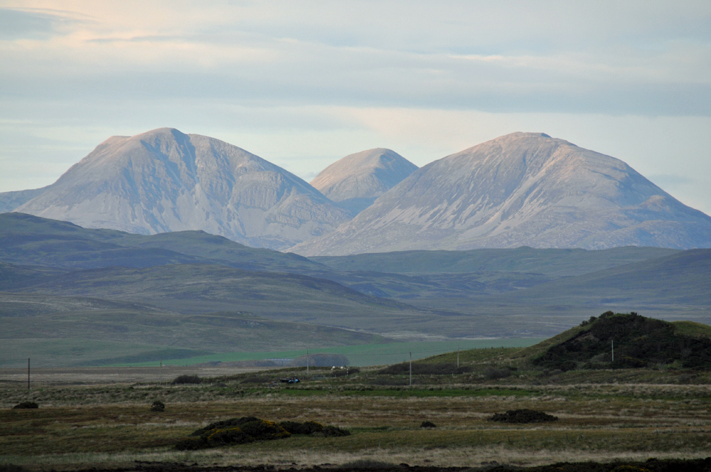 Picture of three mountains in the evening light seen across a wide landscape