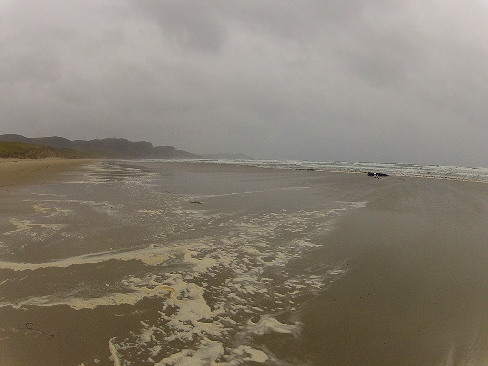 Picture of a beach in a bay on a rainy dark day