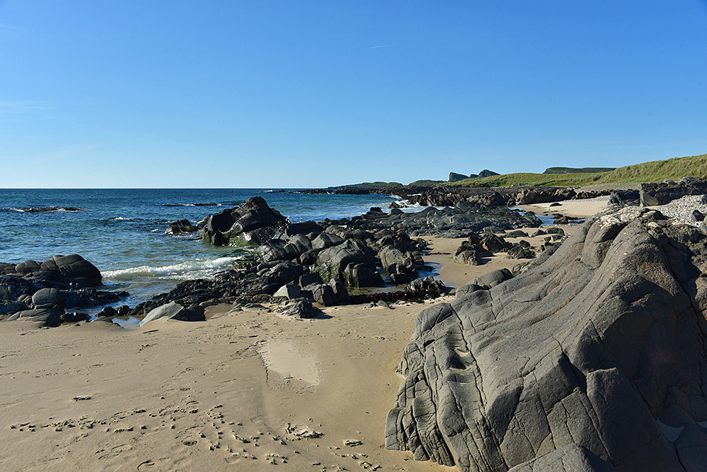 Picture of a view along a mixed coastline with sandy beach and rocks under a sunny blue sky
