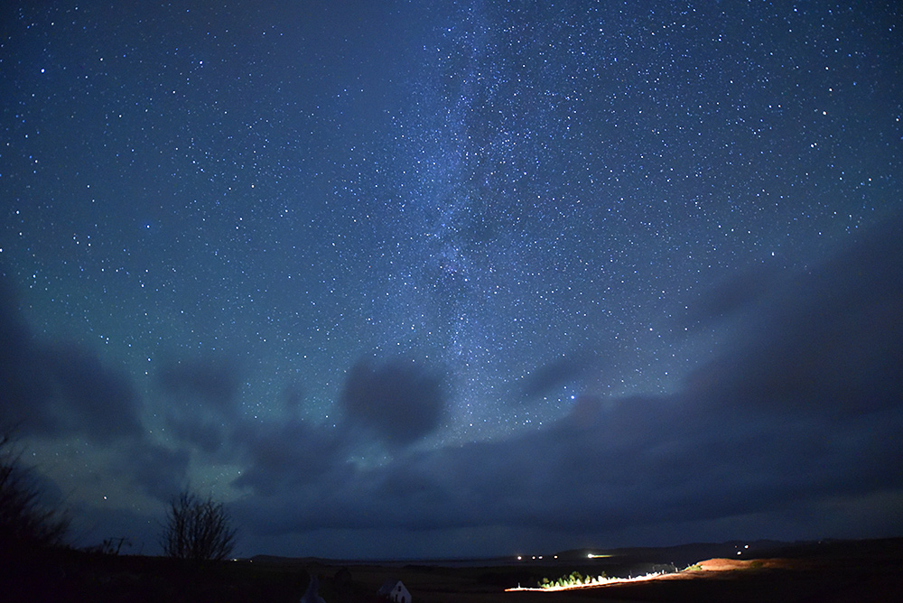 Picture of a night sky over a rural landscape, clouds moving in from the west