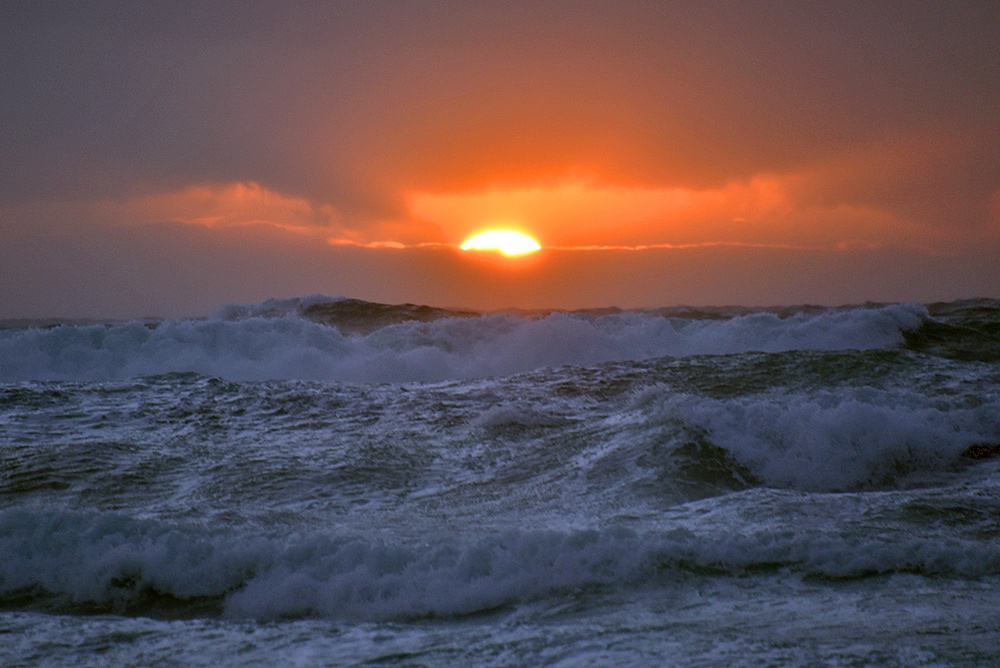 Picture of waves breaking in front of the setting sun