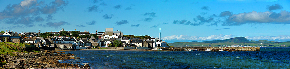 Panoramic picture of a coastal village with a small harbour sheltering behind a pier