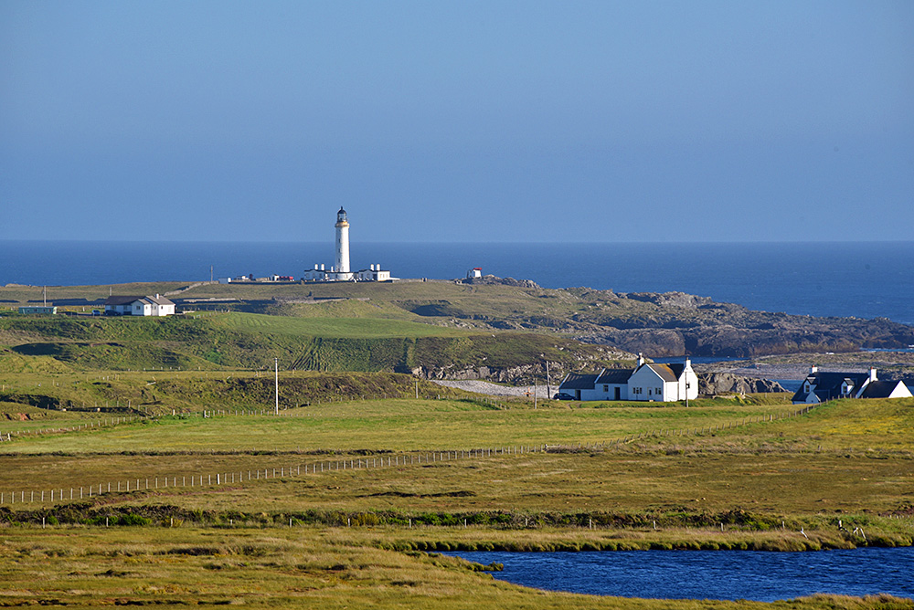 Picture of a few scattered houses with a lighthouse in the background