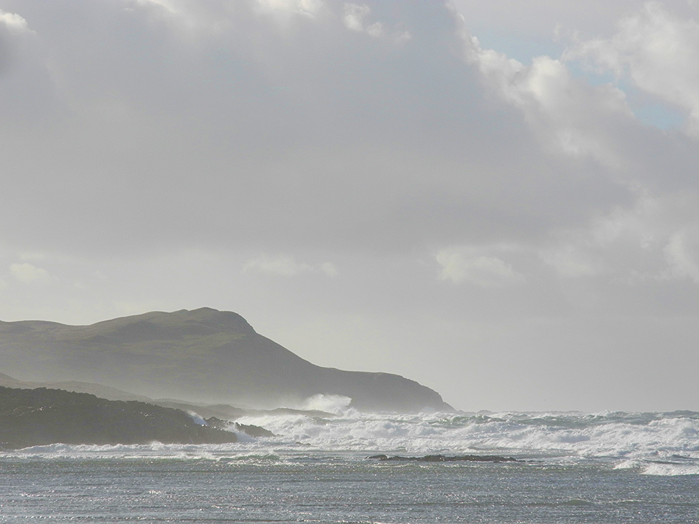 Picture of a big swell with breaking waves rolling into a bay, sunlight under clouds