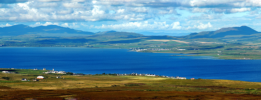 Picture of a view over a sea loch with a village on each side, taken from a hill