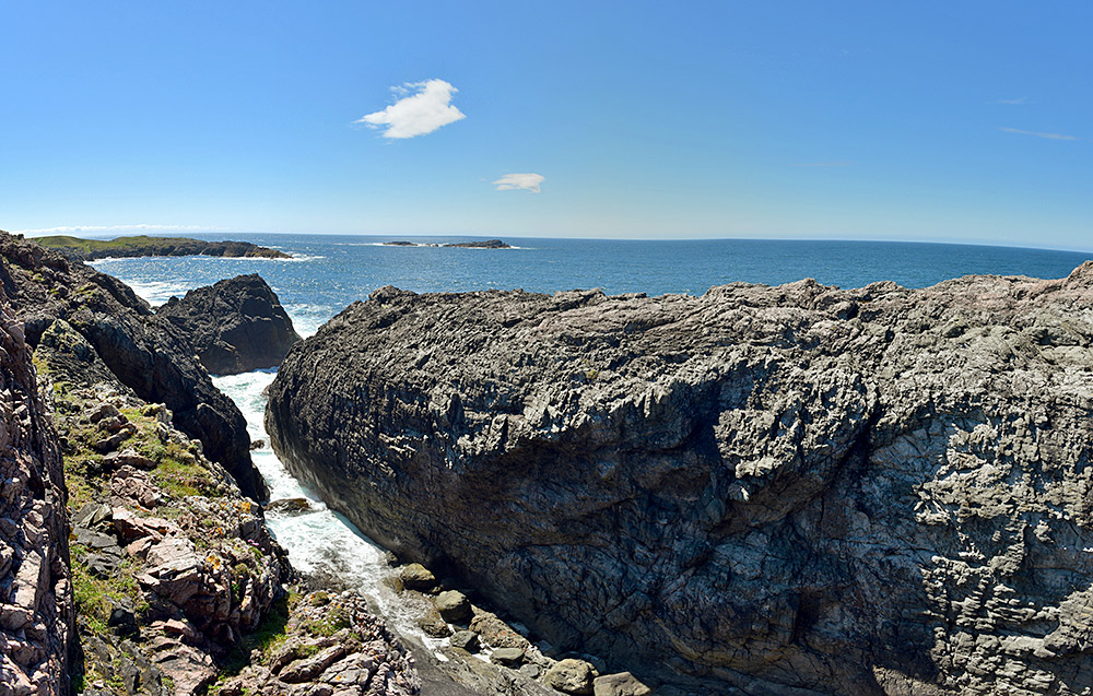 Panoramic picture of a steep cliff cut on a sunny day