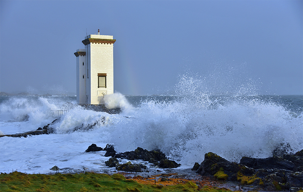 Picture of waves breaking around a white square lighthouse