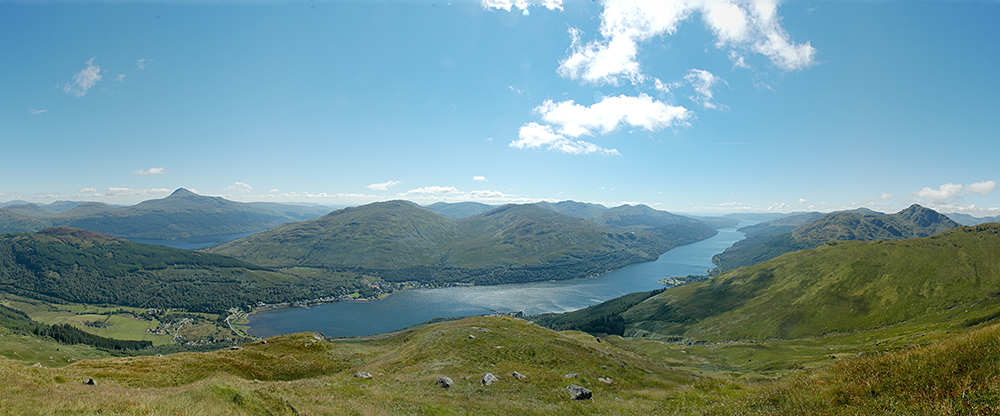 Panoramic picture of a view from a mountain over other mountains, a sea loch and a freshwater loch