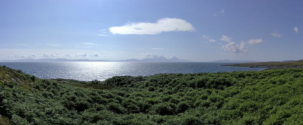 Panoramic picture of a view out to sea from an island on a bright sunny day, the silhouettes of other islands in the haze on the horizon