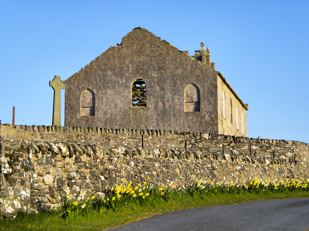 Picture of a church behind a wall, daffodils in front of the wall
