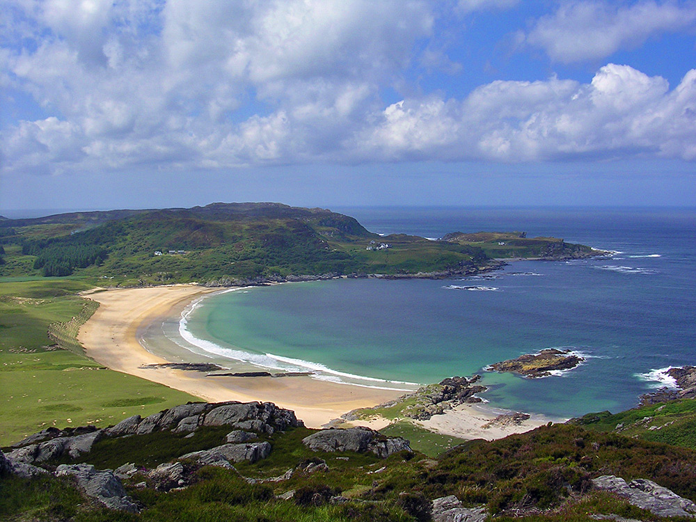 Picture of a view over a bay with a sandy beach from a hill