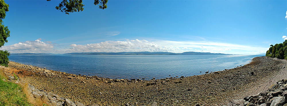 Panoramic picture of a view over a sea loch on a bright sunny day