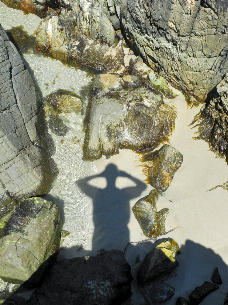Picture of a human shadow over sand and rocks