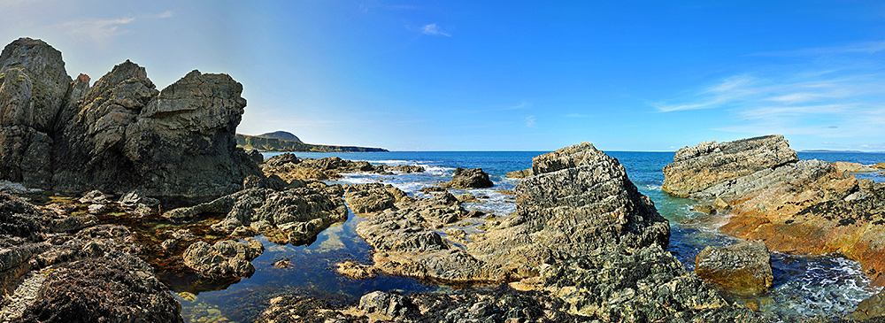 Panoramic picture of a rocky shoreline on a bright sunny day