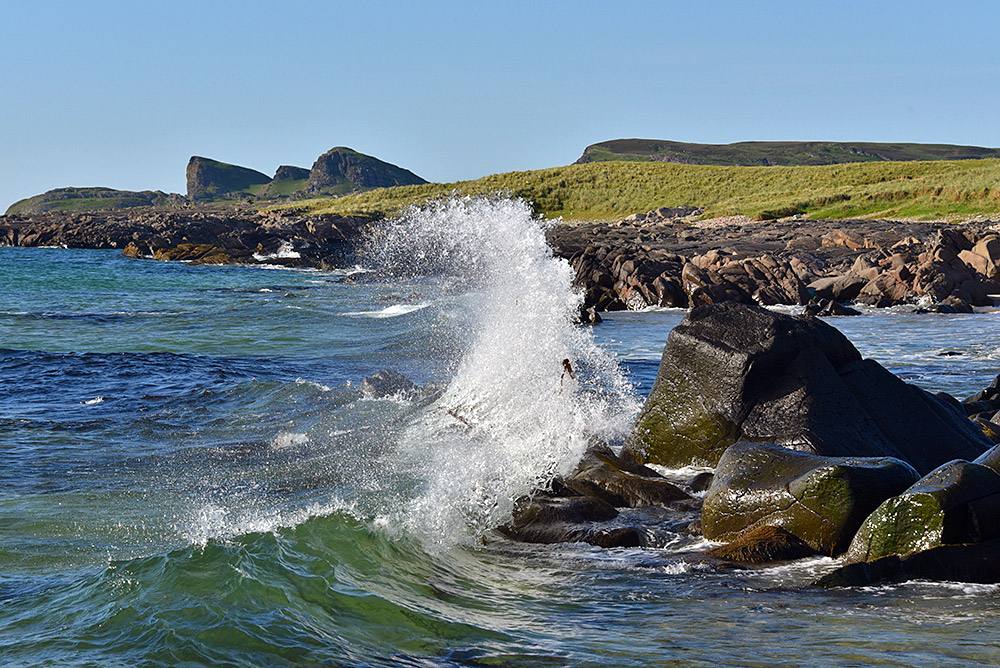 Picture of a small wave splash over rocks in a bay