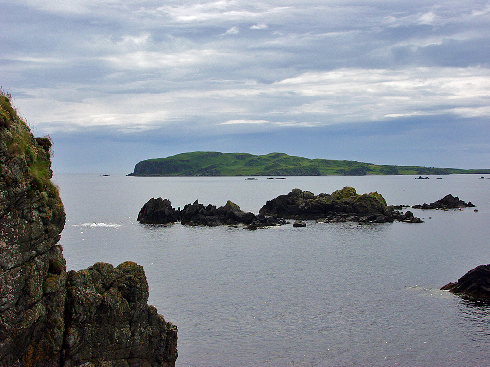 Picture of a view towards a smaller island, also various cliffs and rocks in the sea