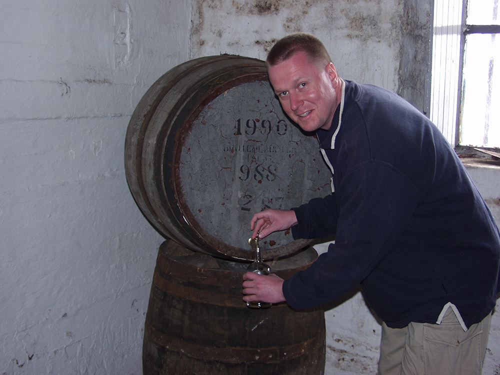 Picture of a man filling a bottle from a whisky cask