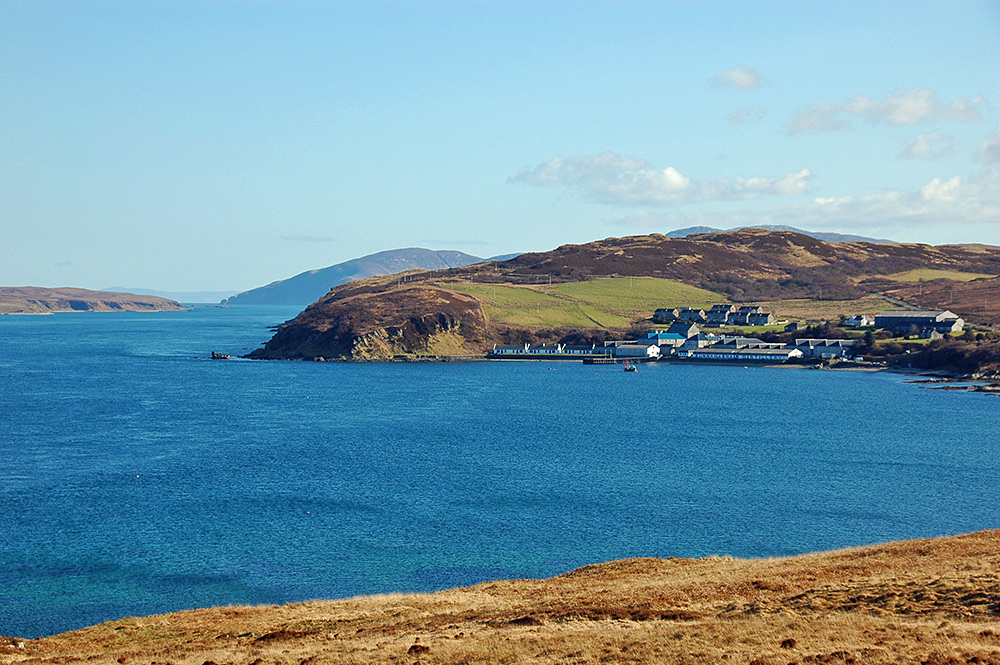 Picture of a small village with a distillery in the sunshine at a sound between two islands