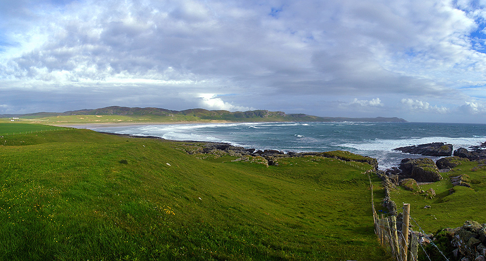 Panoramic picture of a bay with a wide sandy beach, seen from a nearby headland