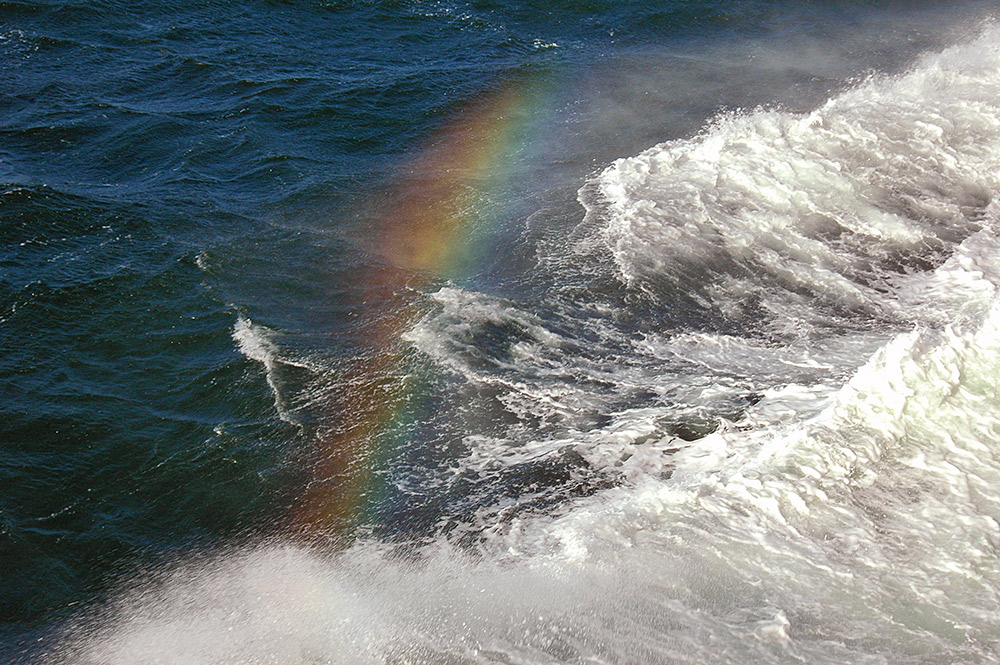 Picture of a rainbow in the spray of a bow wave of a ferry