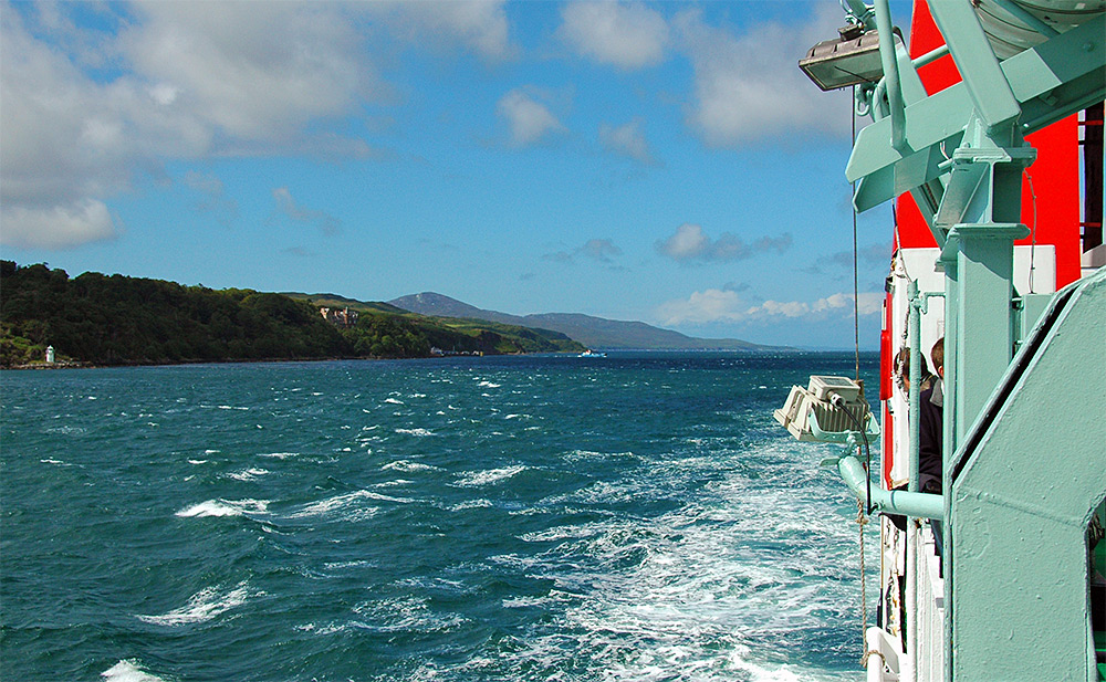 Picture of a view from a ferry travelling down a sound between two islands on a blustery day
