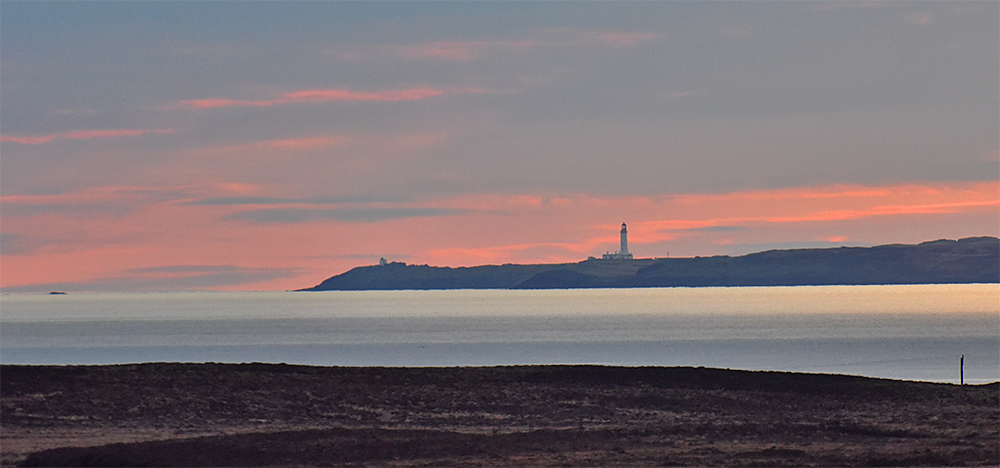 Picture of a view across a sea loch to a lighthouse with a colourful sunset sky behind it