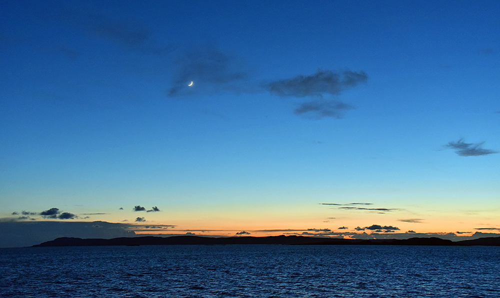 Picture of a Crescent Moon in the gloaming over a peninsula, seen from a ferry